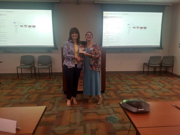 "Joann awarding Sally the weekly ""Best Evaluator"" award"